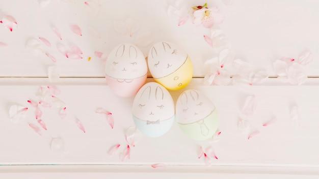 Conjunto de huevos de pascua entre pétalos de flores.