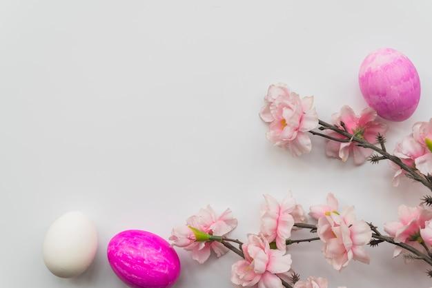 Conjunto de huevos de pascua y ramas de flores frescas.
