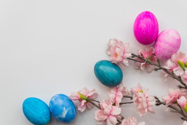 Conjunto de huevos de pascua y ramitas de flores frescas.