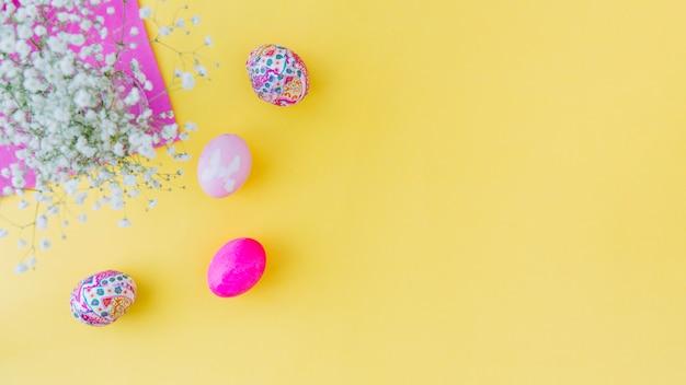 Conjunto de huevos de pascua rosa cerca de flores en servilleta