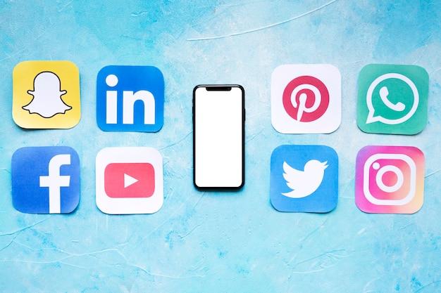 Conjunto de iconos de redes sociales colocados cerca de teléfono inteligente