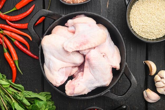 Conjunto de ingredientes de alas pegajosas y sésamo, en sartén de hierro fundido, sobre mesa de madera negra, vista superior plana