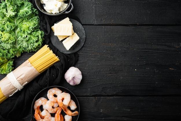 Conjunto de ingredientes de camarones espaguetis, en mesa de madera negra, vista superior plana