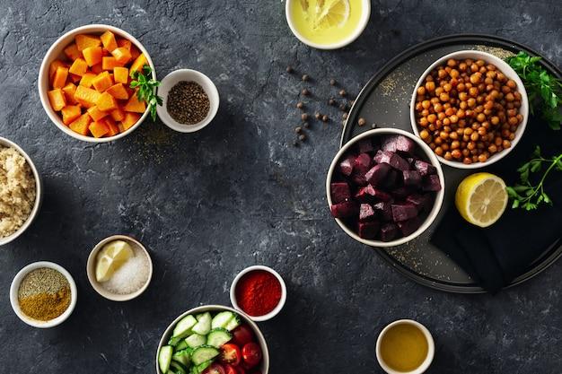 Conjunto de ingredientes vegetarianos saludables para cocinar. garbanzos con especias, calabaza al horno y remolacha, quinua y verduras.