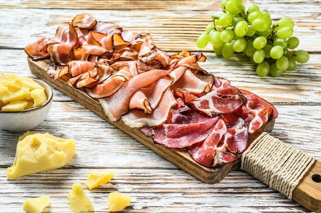 Conjunto de jamón italiano curado en frío, prosciutto, panceta, tocino. fondo de madera blanca. vista superior.