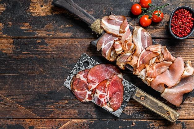Conjunto de jamón italiano curado en frío, prosciutto, panceta, tocino. fondo de madera oscura. vista superior. copie el espacio.
