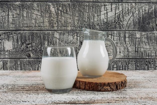 Conjunto de jarra de leche y vaso de leche en una rodaja de madera sobre un fondo de madera gris. vista lateral.