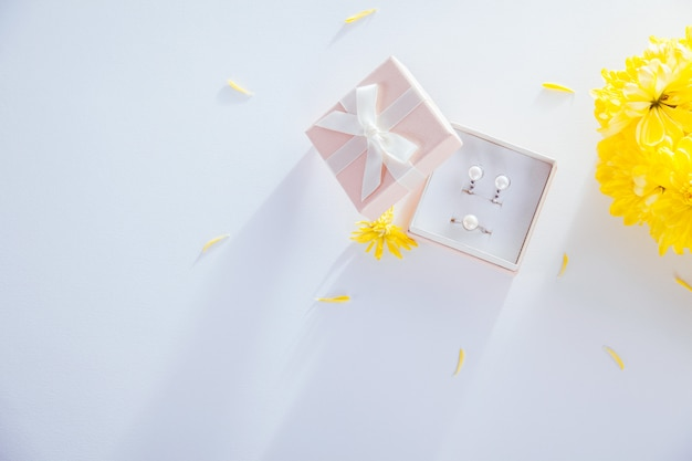 Conjunto de joyas de perlas en la caja de regalo con flores.