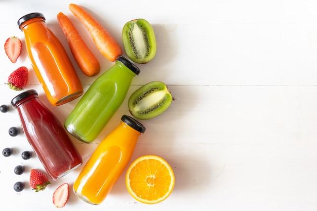 Conjunto de jugo de fruta fresca casera, fuente natural de vitamina c y suplemento, bebidas saludables en botella de vidrio faly yacía sobre madera blanca