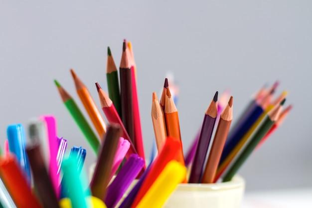 Un conjunto de lápices y marcadores en diferentes vasos. en los marcadores de primer plano, lápices.