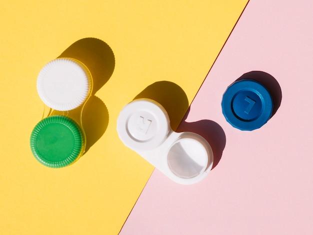 Conjunto de lentes de contacto sobre fondo naranja y rosa