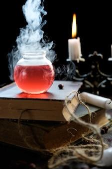 Conjunto de libro de brujería, poción mágica y velas en la mesa
