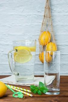 Conjunto de limones, hojas y jarra de limón sobre un paño blanco sobre una superficie de madera y blanca. vista lateral.