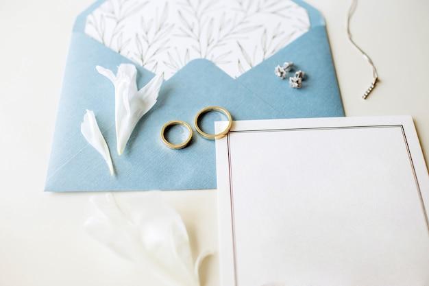 Conjunto de lujo de invitaciones de boda, anillos de boda, accesorios elegantes de la novia sobre un fondo blanco.