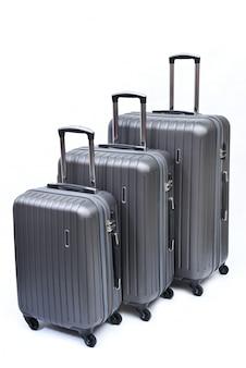 Conjunto de maletas grises grandes, medianas y pequeñas aisladas en blanco.