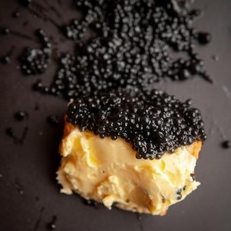 Conjunto de mantequilla y caviar negro sobre un pan sobre fondo oscuro. vista de ángulo alto.