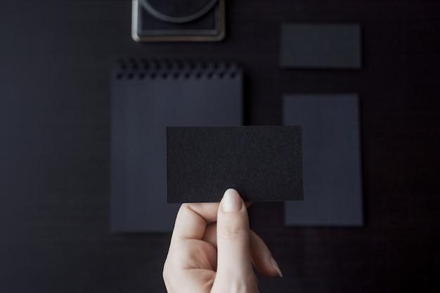 Conjunto de maquetas negras sobre oscuro, mano femenina sosteniendo una tarjeta de visita