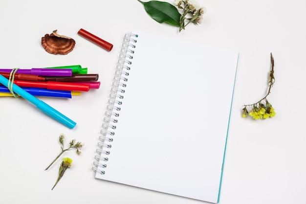 Conjunto de marcadores de punta de fieltro en diferentes colores y un cuaderno de bocetos en blanco.
