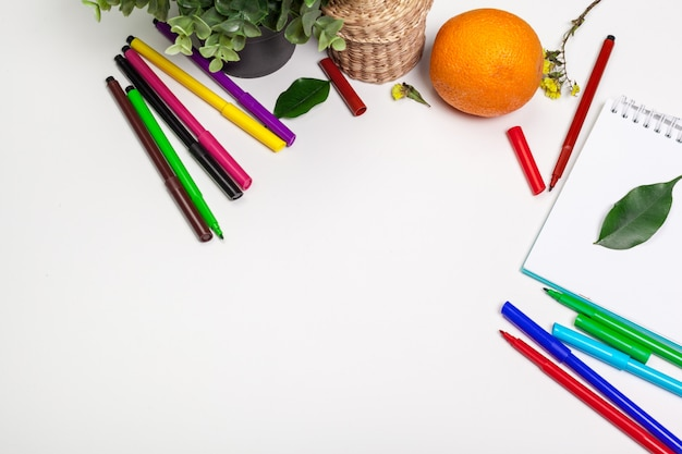 Conjunto de marcadores de punta de fieltro en diferentes colores y un fondo de cuaderno de bocetos en blanco