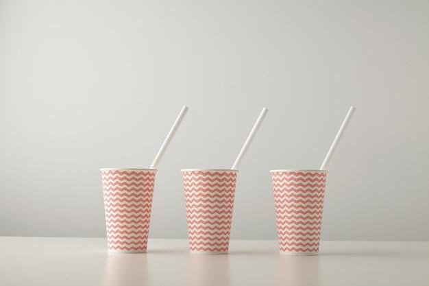 Conjunto minorista de tres vasos de papel decorados con un patrón de línea roja y con una pajita blanca en el interior aislado en una mesa blanca