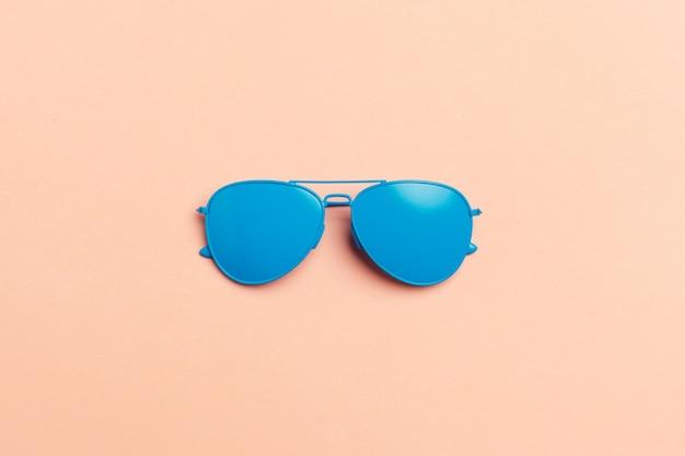 Conjunto de moda plana: gafas de sol sobre fondos pastel. el verano de la moda se acerca concepto.