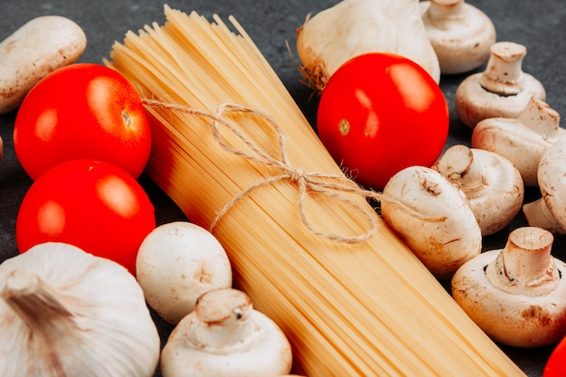 Conjunto de un montón de pasta de espagueti y tomates y champiñones blancos sobre un fondo gris con textura. vista de ángulo alto.
