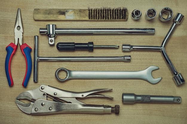 Conjunto de muchas herramientas de mano en el piso de madera marrón. vista superior de la herramienta artesano en mesa de madera. vista superior y fotograma completo. concepto de técnico o ingeniero.