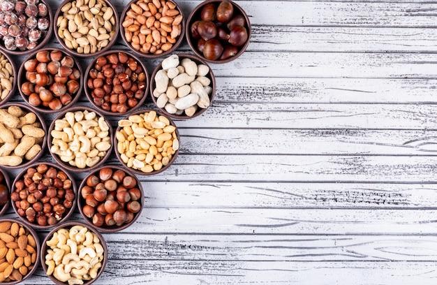 Conjunto de nueces, pistachos, almendras, maní y una variedad de nueces y frutas secas en un mini tazón diferente en forma de ciclo sobre una mesa de madera blanca
