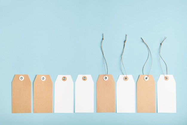 Conjunto de ocho etiquetas de precio de papel en blanco con una cuerda anudada sobre un fondo azul.