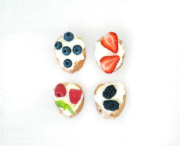 Conjunto de pequeños bocadillos dulces con queso crema y bayas frescas del bosque