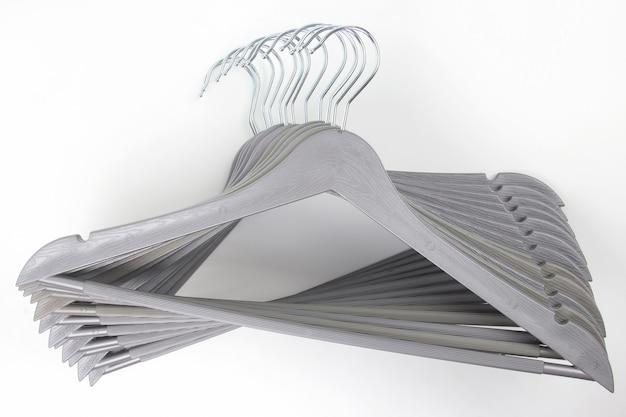 Conjunto de perchas de ropa gris sobre un fondo blanco.