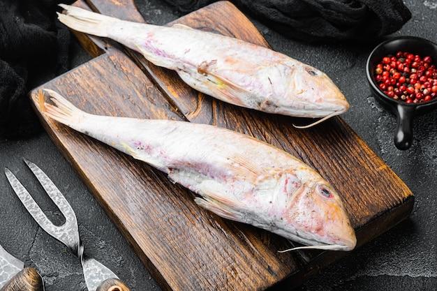 Conjunto de pescado entero de salmonete o barabulka fresco crudo, con ingredientes y hierbas, sobre fondo de mesa de piedra oscura negra