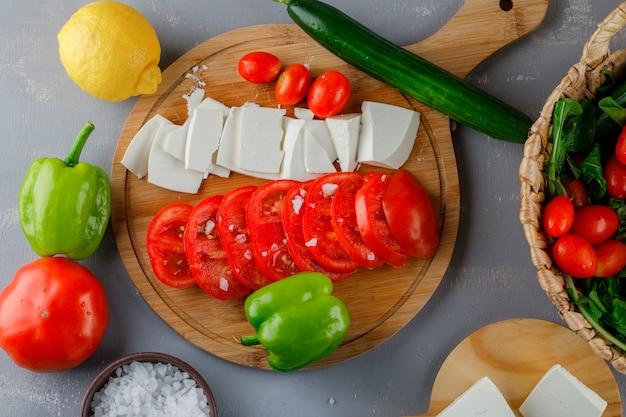 Conjunto de pimiento verde, limón, pepino, sal y queso en rodajas y tomates en una tabla de cortar sobre una superficie gris