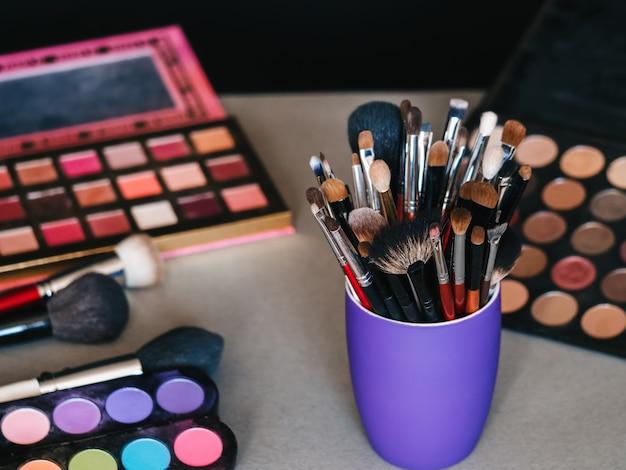 Conjunto de pinceles de maquillaje en el fondo de paletas profesionales de sombra de ojos