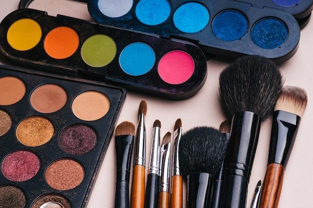 Conjunto de pinceles de maquillaje y paleta con sombras de ojos multicolores