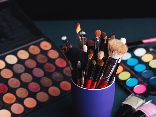 Conjunto de pinceles de maquillaje profesional en el fondo de una paleta con sombras de ojos de colores y cosméticos.