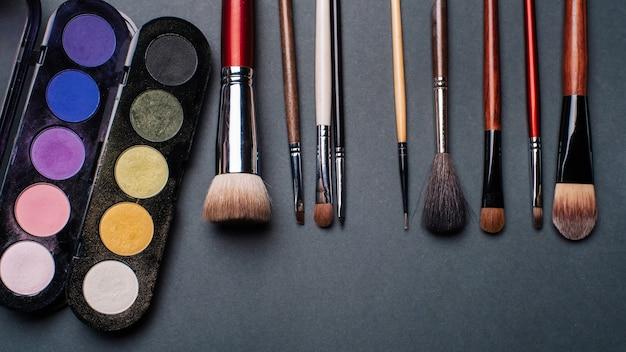 Conjunto de pinceles y paletas con sombras de ojos de colores.