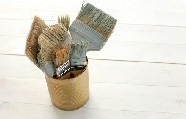 Conjunto de pinceles sobre suelo de madera.