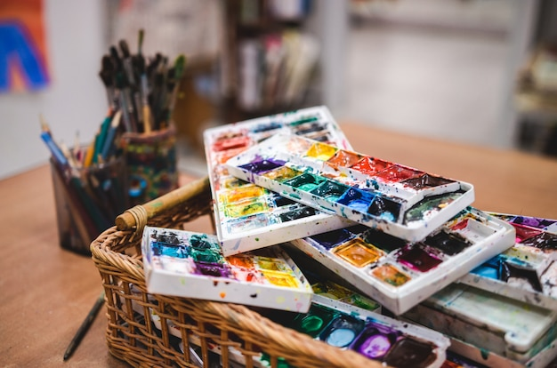 Conjunto de pinturas de acuarelas en cesta. estudio creativo