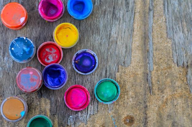 Conjunto de pinturas gouache y acuarela para dibujar, herramientas artísticas en madera vieja. herramientas para el trabajo creativo. concepto de regreso a la escuela y arte creativo. vista superior. copyspace