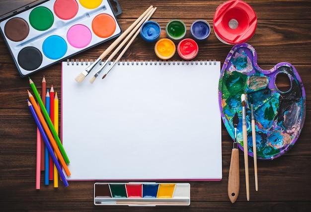 Conjunto de pinturas, lápices, herramientas para pintar y hoja de papel blanco en blanco.