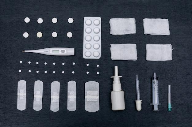 Conjunto de pipeta, vendaje, aerosol nasal y pastillas, curitas y termómetro.