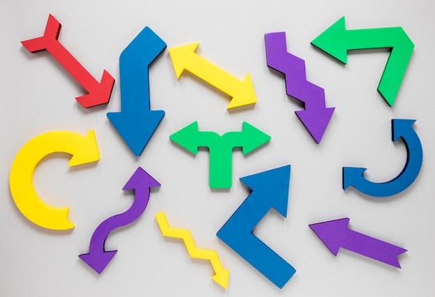 Conjunto plano laico de flechas de colores sobre fondo blanco
