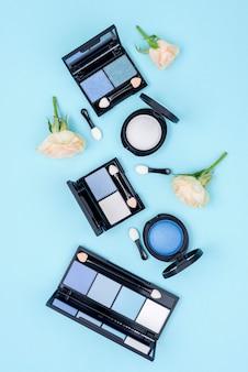 Conjunto plano de productos de belleza sobre fondo azul.