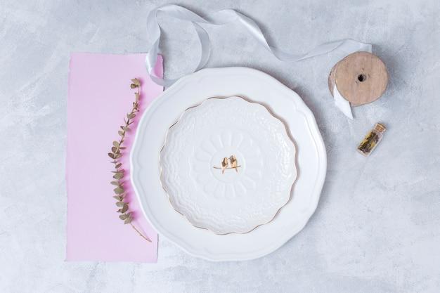 Conjunto de planta junto a plato, papel y bobina de cinta.