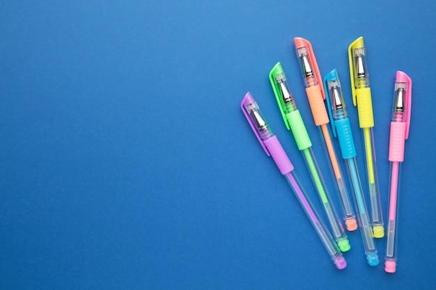 Conjunto de plumas de colores sobre fondo de papel azul con espacio de copia