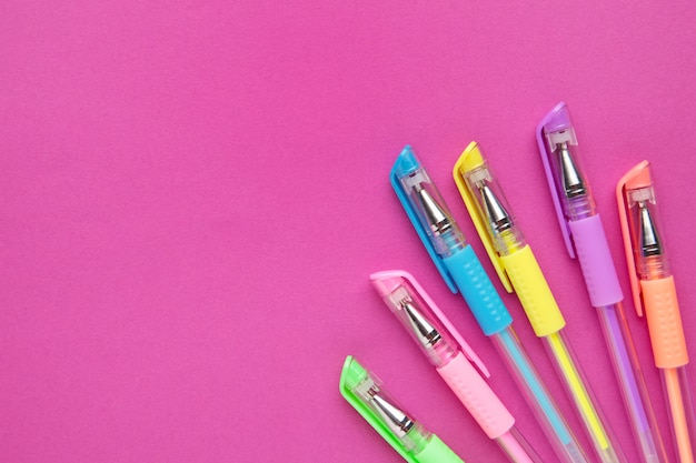 Conjunto de plumas de colores sobre fondo de papel rosa con espacio de copia