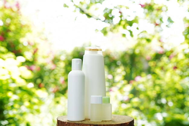 Conjunto de productos de cuidado de la piel del cuerpo en la naturaleza, copia espacio. champú, gel, aceite
