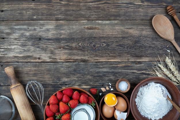 Un conjunto de productos naturales para hacer una tarta sobre fondo de madera