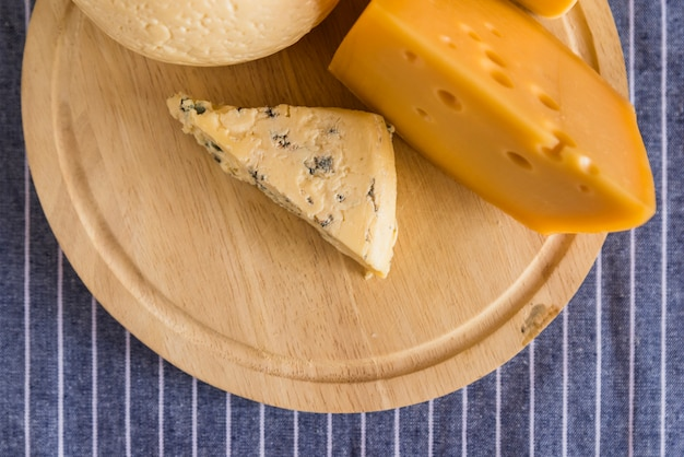 Conjunto de queso fresco sobre plancha de madera sobre mesa